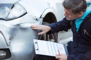 insurance adjuster inspects car damage