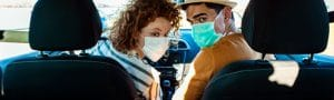 Image of people in a car wearing face masks